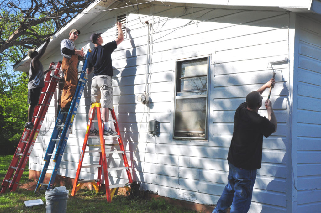 Members of the 366th Training Squadron paint the exterior of a Wichita Falls, Texas, home during Christmas in Action April 24, 2010. Christmas in Action is a program that has renovated the homes of low-income elderly and disabled homeowners in Wichita County for 27 years. (U.S. Air Force photo/Airman 1st Class Valerie Hosea)